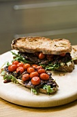 Steak sandwiches with fried tomatoes and rocket