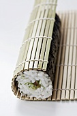 Sushi filled with tuna and negi (Japanese spring onions) being rolled