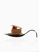 A layered blini cake on a curved spoon (molecular gastronomy)