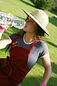 A young woman in a straw hat and gardening gloves drinking mineral water from a bottle