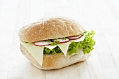 A bread roll filled with cheese, radishes and cress