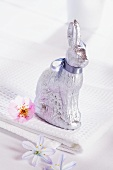 A chocolate bunny wrapped in silver paper