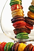 A stack of colourful macaroons in and in front of a glass