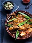 Chicken with okra pods, tomatoes and onions in a tanjine