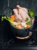 Suppenhuhn im Kochtopf mit Gemüse