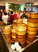 Lots of bamboo steamers filled with dim sum on a trolley in a Chinese restaurant