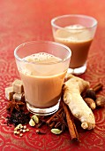 Two glasses of chai tea with spices and sugar cubes