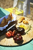 Black tomatoes, a baguette and olive oil on a garden table