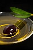 Ein Schälchen Olivenöl mit schwarzer Olive
