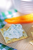 A cracker with a cream cheese and rocket spread