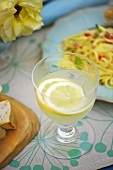 Zitronenlimonade im Glas neben Nudelgericht