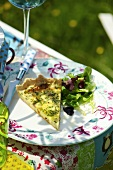 A piece of cheese quiche with a mixed leaf salad on a garden table