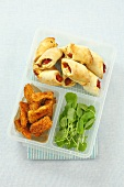 Tomato pastries, chicken fingrers and watercress in a plastic box