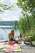 Junge Frau beim Grillen am See