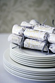 A stack on plates with Christmas crackers on top