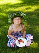 A little girl with a crown of flowers and a strawberry pancake