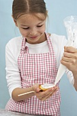 A girl decorating a biscuit lolly with icing sugar