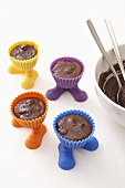 Chocolate cake dough in muffin cases with feet