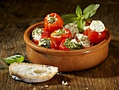 Cherry tomatoes stuffed with a herb and cream cheese filling and mini peppers stuffed with a pesto and cream cheese filling