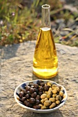 Olive oil in carafe, two types of olives in bowl out of doors