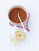 Tomato sugo in a small pan and uncooked tagliatelle