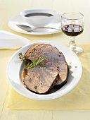 Several slices of roast beef with gravy and herbs