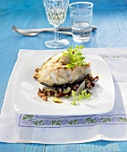 Cod steak with bacon, mushrooms, olives and capers