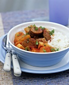 Fried sausage slices with root vegetables and rice