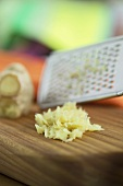 Grated ginger with a grater on a wooden board