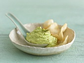 Avocado and wasabi dip with spoon in a porcelain dish