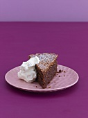 A piece of chocolate almond cake with whipped cream
