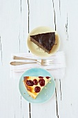 A piece of cherry cheesecake & a piece of chocolate poppy seed cake