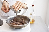Man putting pepper on fillet steaks in a frying pan