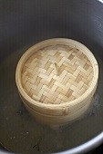 Bamboo steamer in a large pan with white wine stock