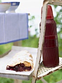 A cherry strudel with Thermos flask out of doors