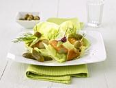 Schillerlocken (smoked dogfish) on cocktail sticks on lettuce