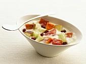 A bowl of fruit salad in vanilla cream