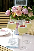 Three glasses of lemon mousse with raspberries out of doors