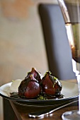 Three figs poached in red wine and blackberry sauce