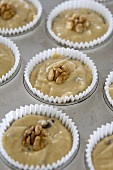 Banana & chocolate muffin mixture with walnuts in muffin tin