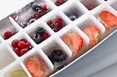 Ice cubes with frozen berries in an ice cube tray