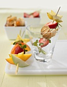 Two fruit skewers with different fruits