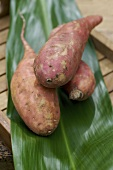 Three sweet potatoes on a banana leaf