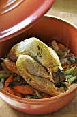 Braised guinea fowl with vegetables in a terracotta pot