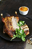 Honey-glazed duck, partly carved, with carrots