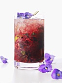 A glass of berry cocktail with flowers