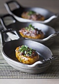 Three stuffed baked potatoes in cast-iron cookware