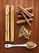 Zimtrinde, -stange und -pulver auf Holzuntergrund