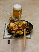 Potato and bacon hash in a frying pan and a glass of beer