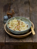 Cabbage salad with caraway seeds and bacon in pottery bowl